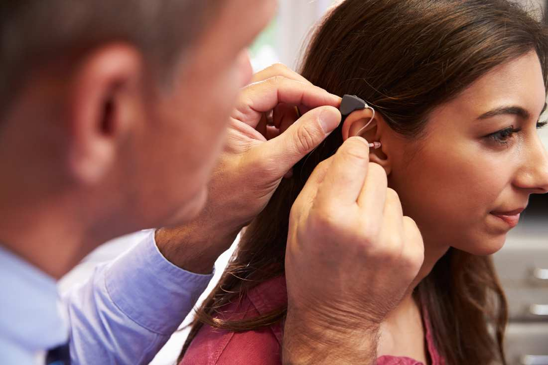 doctor installing a hearing aid on woman