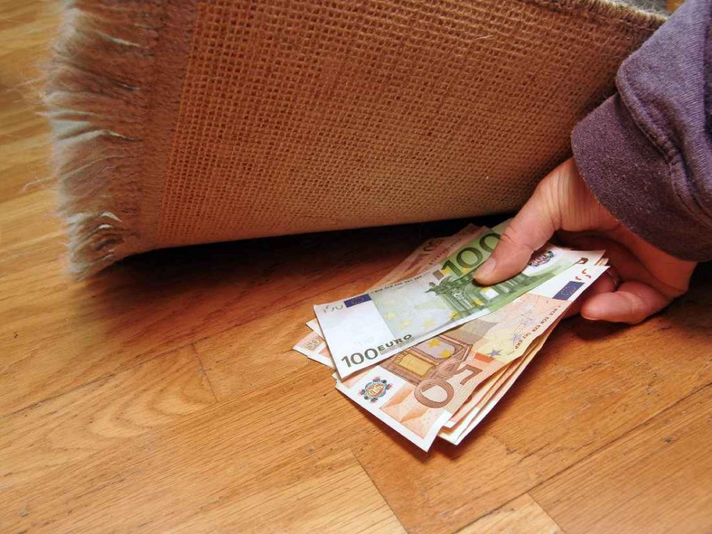 Person outting money underneath a rug