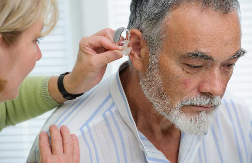 an older man having a hearing aid implanted