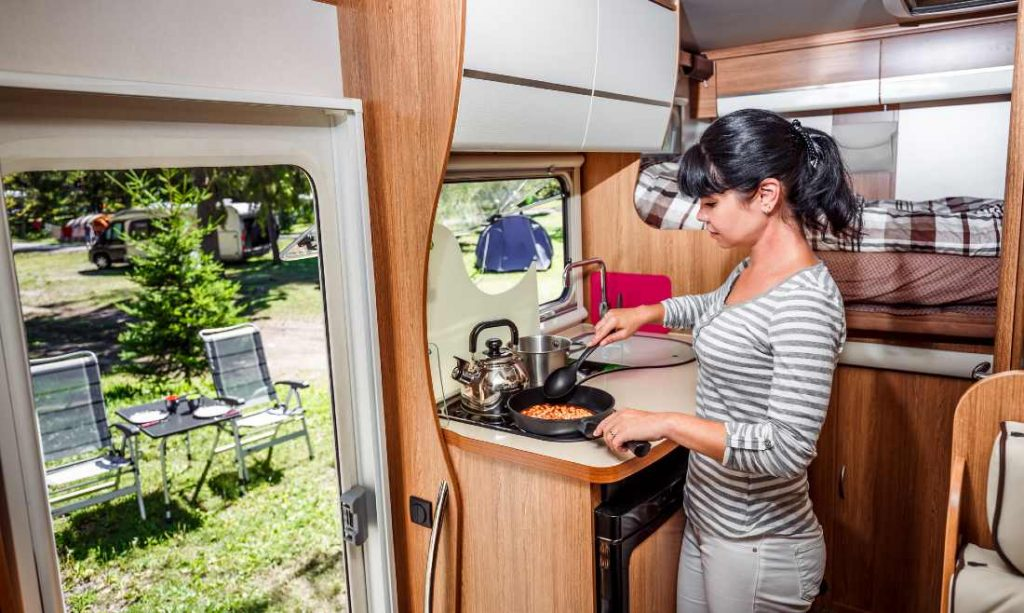 woman cooking food on a gas stove in a campervan