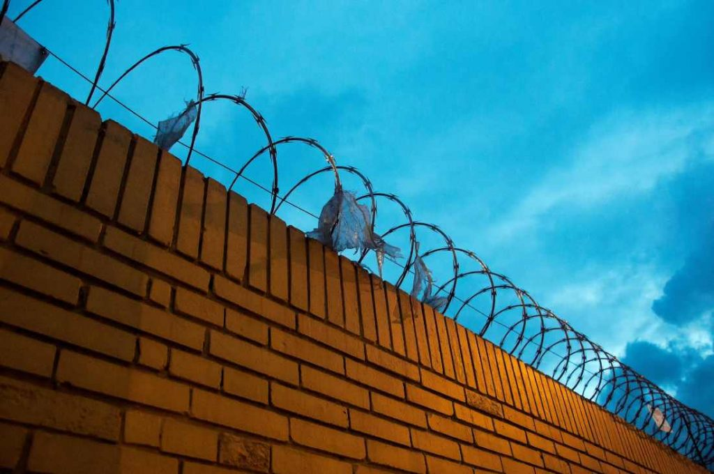 a brick wall with barbed wire on top