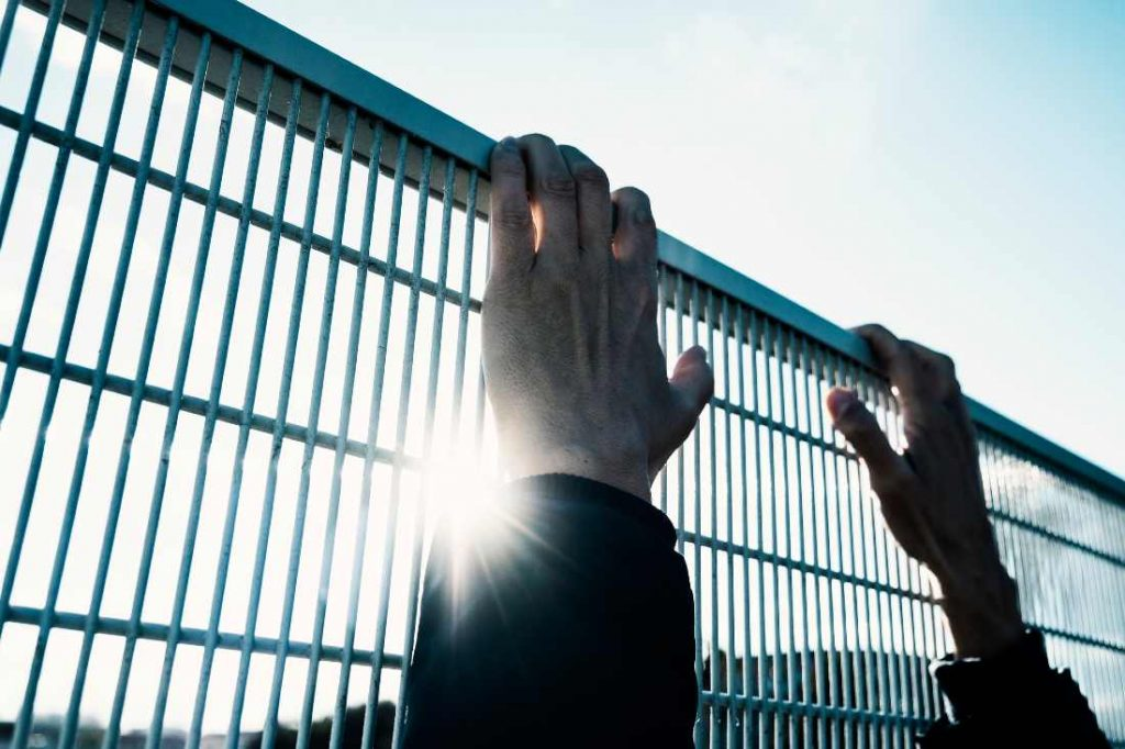 hands reaching over a metal fence