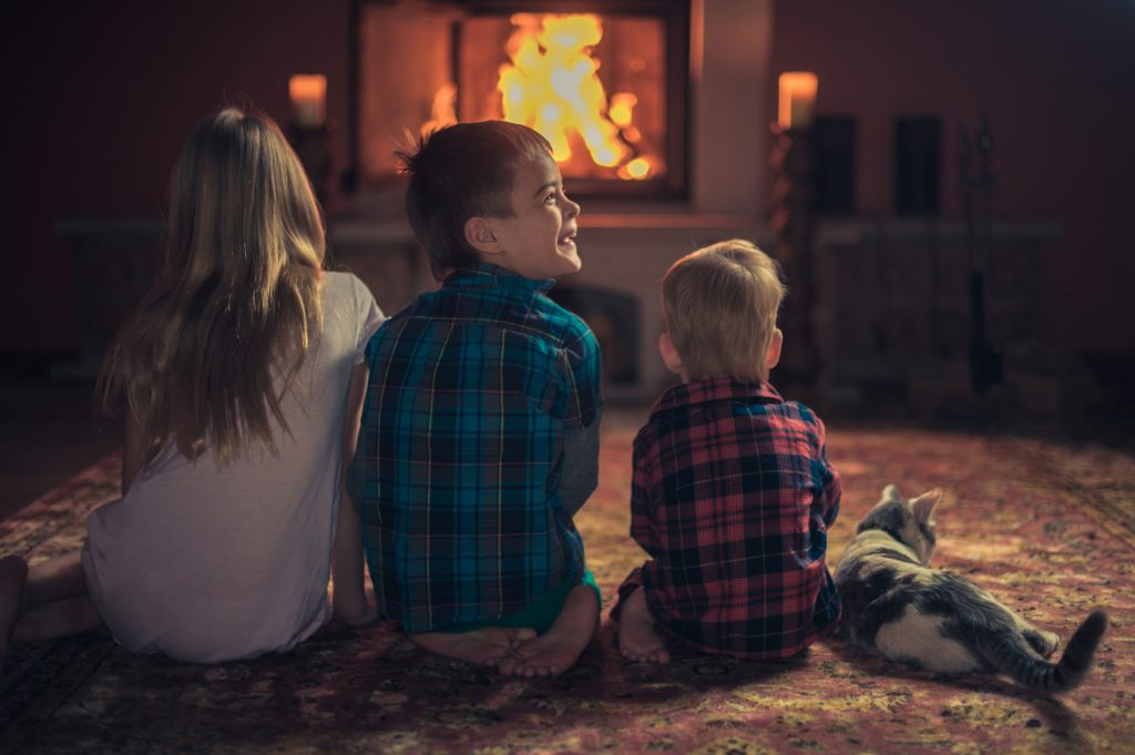 children and cat by the fireplace