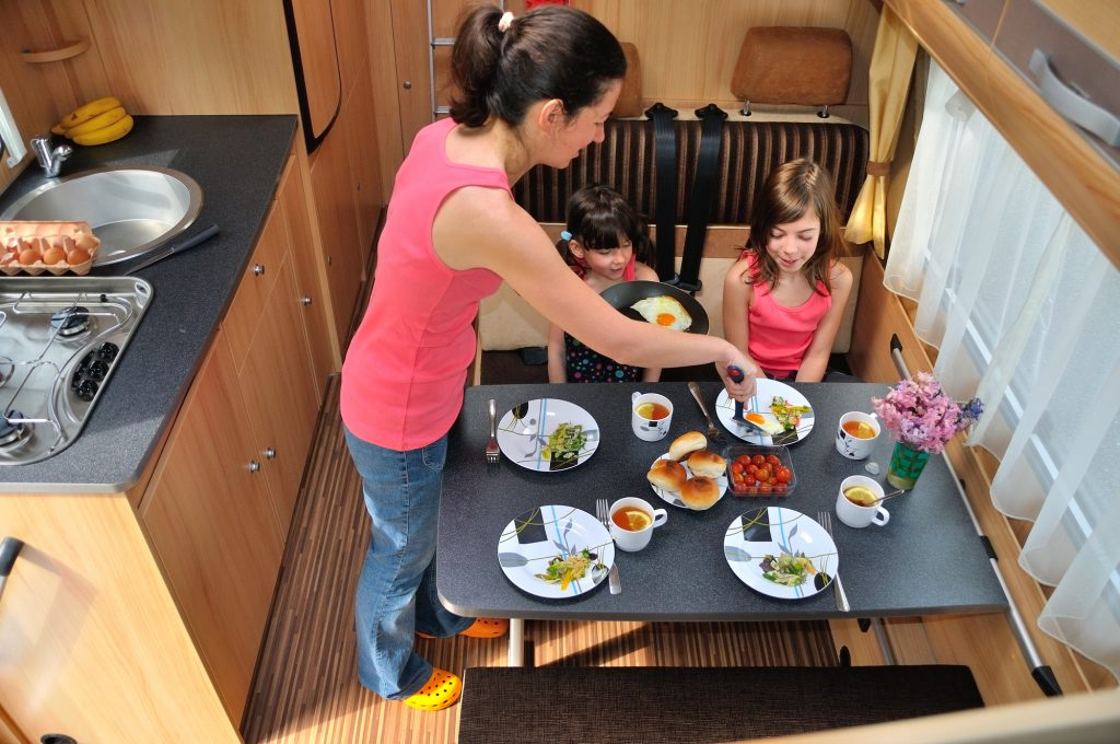 family enjoying cooking in the kitchen of a caravan