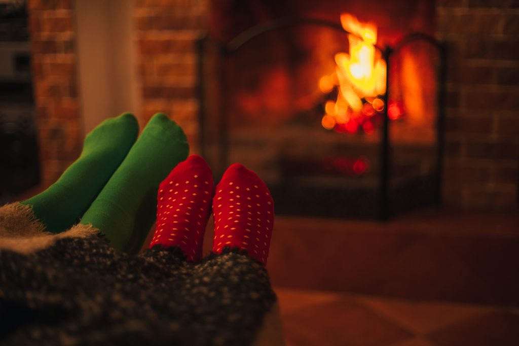 man and woman with feet up by the fireplace