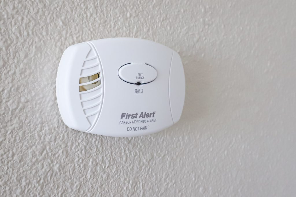 carbon monoxide detector affixed on a plain white wall