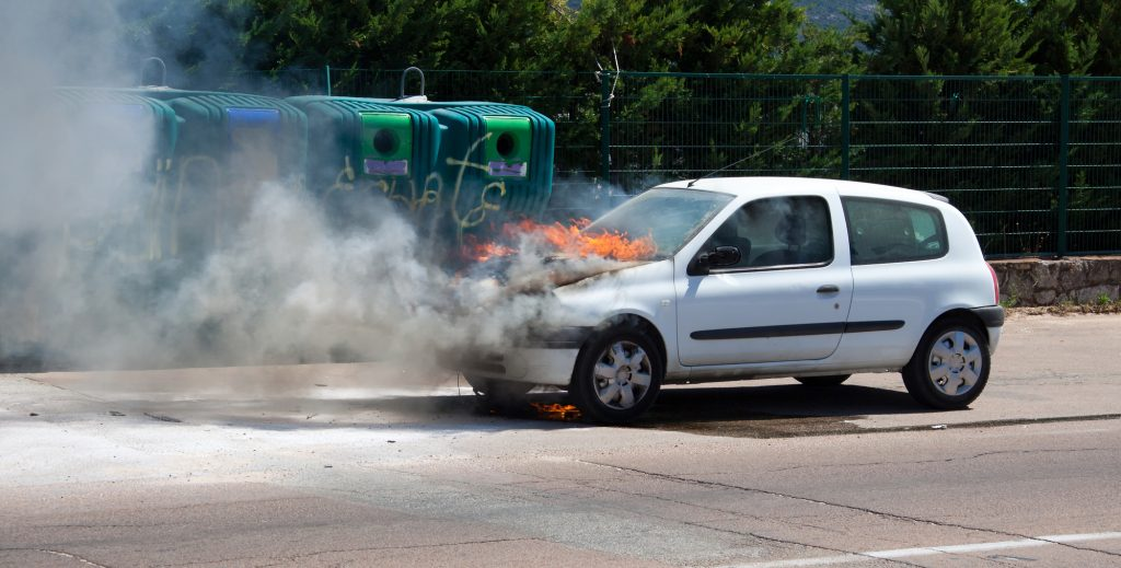 an old renault clio with the front on fire