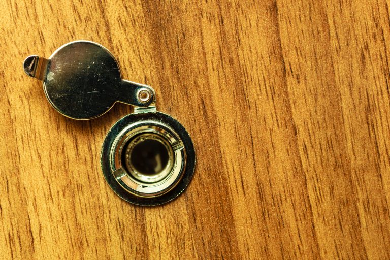 a traditional peephole on a wooden door
