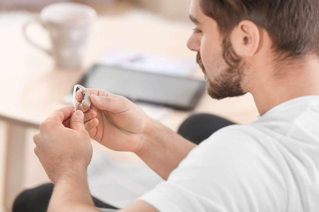 young man looking at hearing aid