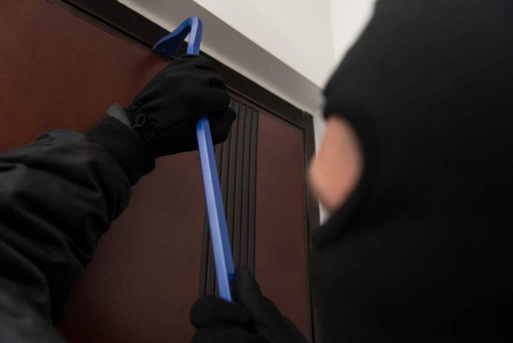 burglar using a crowbar to open a garage