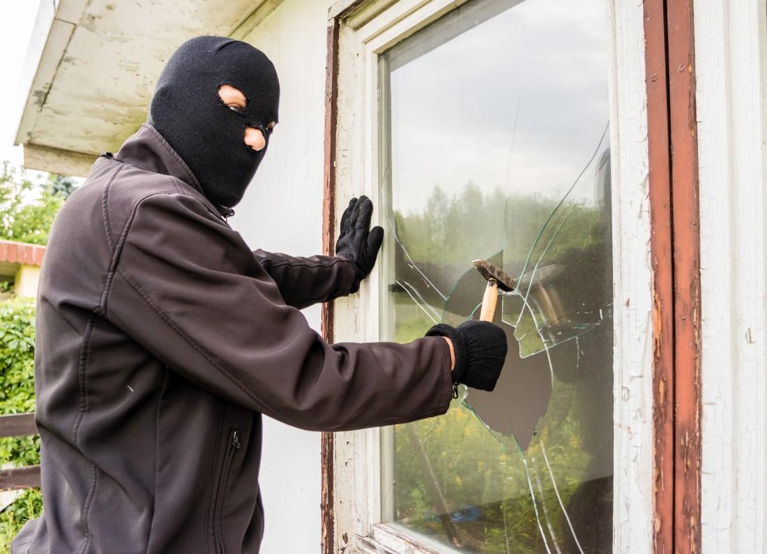 man with a balaclava hammering through a window