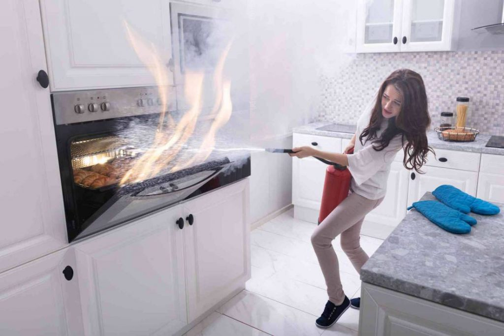 woman using fire extinguisher to stop fire