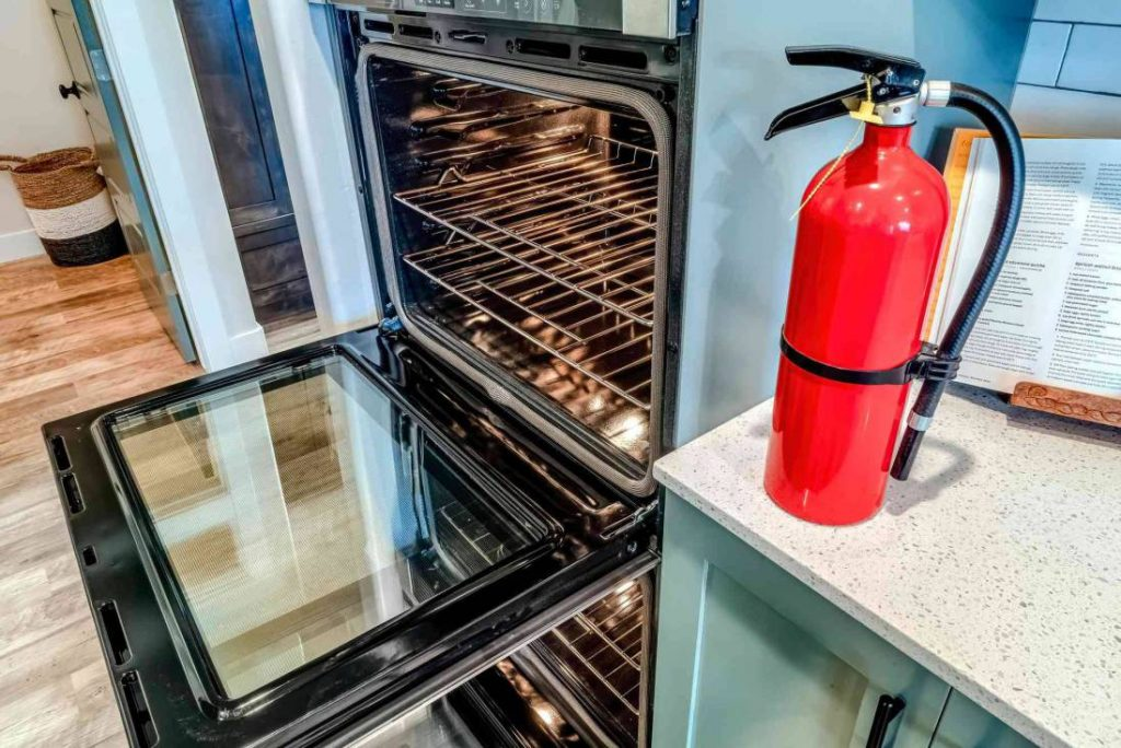 red fire extinguisher and electric oven open doors